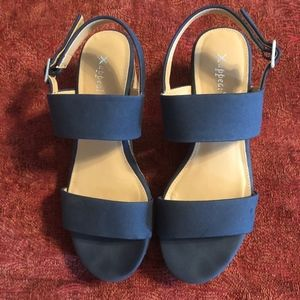 Navy blue wedge sandals with faux cork base.